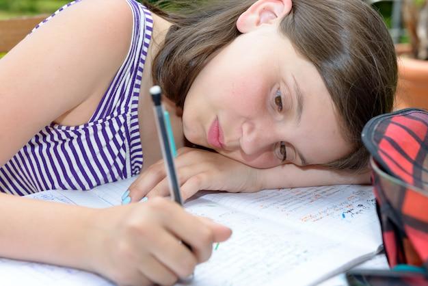 Bored teenage girl is doing her homework