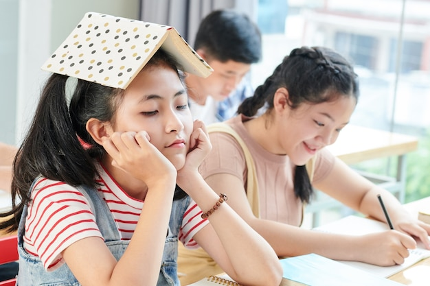Bored teenage girl sitting at school desk with opened book on her head while her smiling classmate writing in copybook