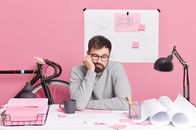 退屈な疲れた男の建築家は、コワーキングスペースでの自宅のポーズから建築図面の作品に疲労感があるという眠そうな表情をしています