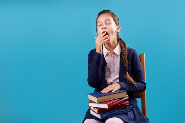 Bored tired yawning schoolgirl in uniform with pile of books sitting on chair, lack of motivation to study and read concept