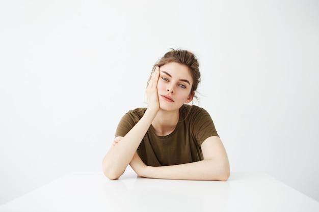 Скучно устал молодая женщина студент с булочкой, сидя за столом