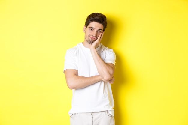 Uomo annoiato e divertito che guarda con indifferenza, in piedi in abiti bianchi su sfondo giallo.