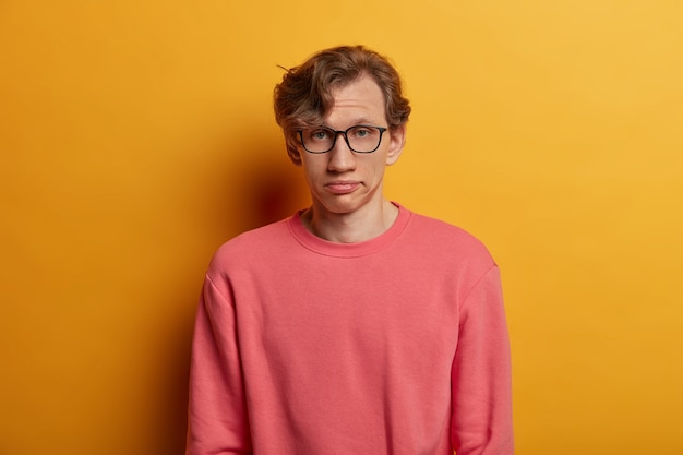 Studente maschio annoiato non impressionato guarda seriamente, ha un'espressione affaticata, indossa occhiali da vista e maglione rosa, sospira dalla stanchezza, isolato sul muro giallo. espressioni del viso