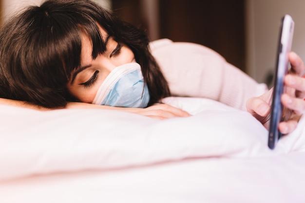 携帯電話を使用して彼女の顔に医療呼吸マスクを呼吸することで自宅で退屈女性。パンデミックコロナウイルス、ウイルスcovid-19。隔離、感染防止のコンセプト。携帯電話に焦点を当てます。