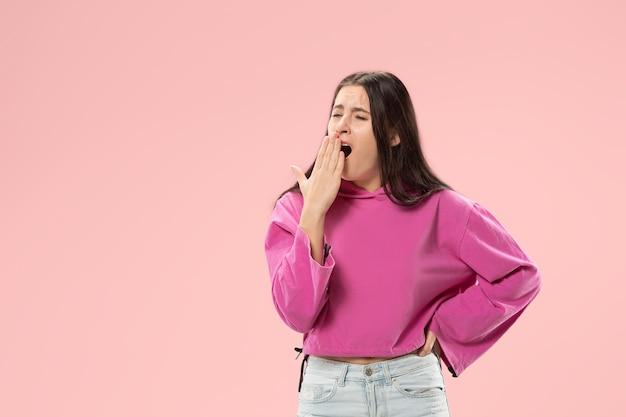 지루한 여자. 지루하고 지루하고 지루한 개념. 젊은 꽤 백인 감정적 인 여자. 인간의 감정, 표정 개념. 유행 분홍색 벽에 절연