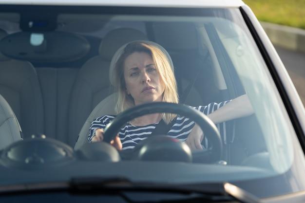 Скучающая женщина-водитель раздражена за рулем автомобиля, усталая несчастная женщина в автомобиле в плотной пробке