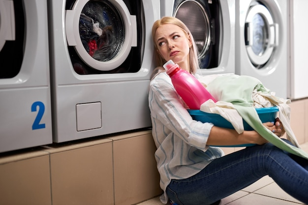 汚れた服と洗剤のピンクのボトルを洗面器に持っている退屈な女性は、洗濯機に寄りかかって床に座って、一人で落ち込んで、洗濯場に座っています