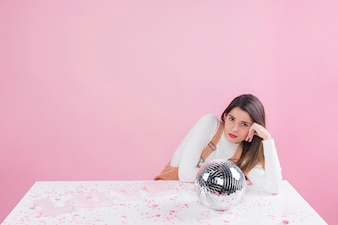 Bored woman sitting at table with disco ball
