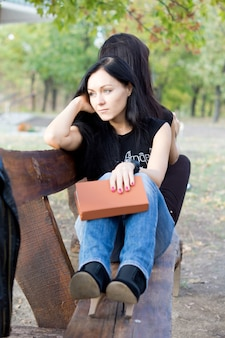 Bored woman sitting on a rustic wooden bench in the countryside with her closed book in her hand staring off into space daydreaming