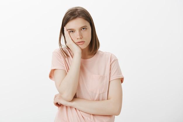 Скучающая женщина-студентка опирается на ладонь и смотрит равнодушно и сонно