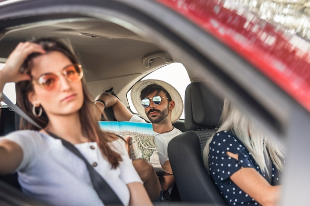Bored woman travelling by car in front of man looking at map for direction
