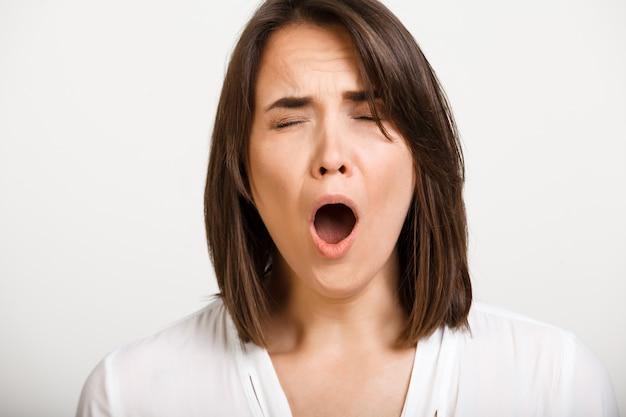 Bored woman yawning, feel sleepy