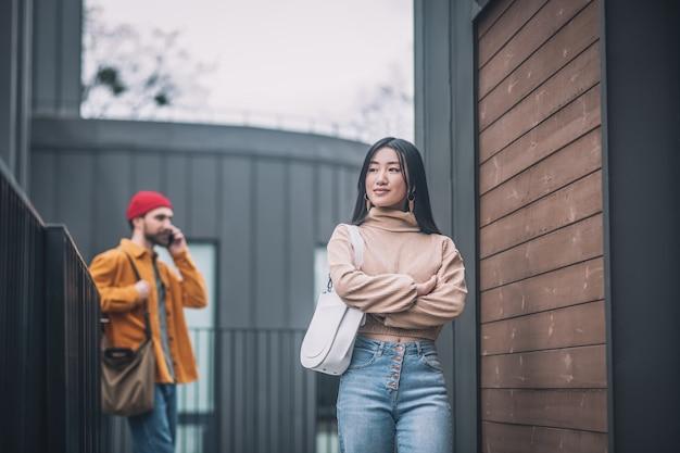 Скучающая женщина. молодая женщина скучает, пока ее бойфренды разговаривают по телефону