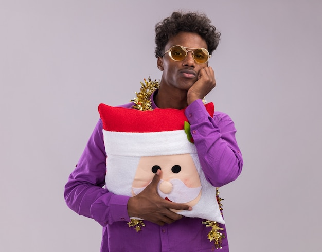 Bored young afro-american man wearing glasses with tinsel garland around neck holding santa claus pillow keeping hand on chin looking at camera isolated on white background