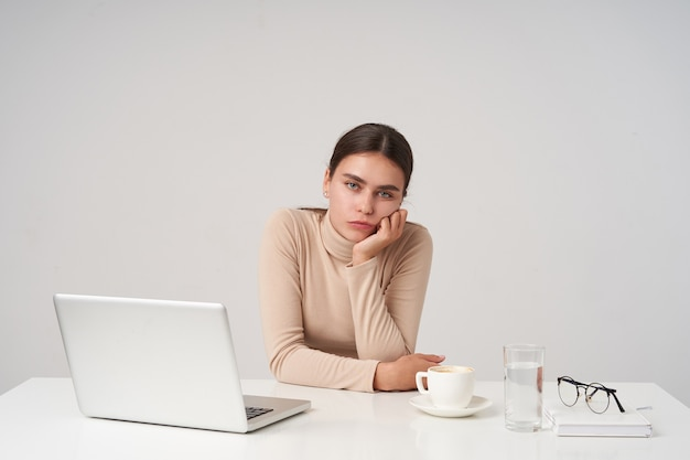 Bored young attractive brunette female leaning her head on raised hand while sitting at table, working with laptop at office, keeping her lips folded while looking