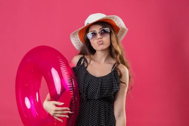ピンクの空間の上に立ってよそ見インフレータブルリングを保持しているサングラスを身に着けている夏帽子の水玉模様のドレスで退屈若い美しい旅行者の女の子