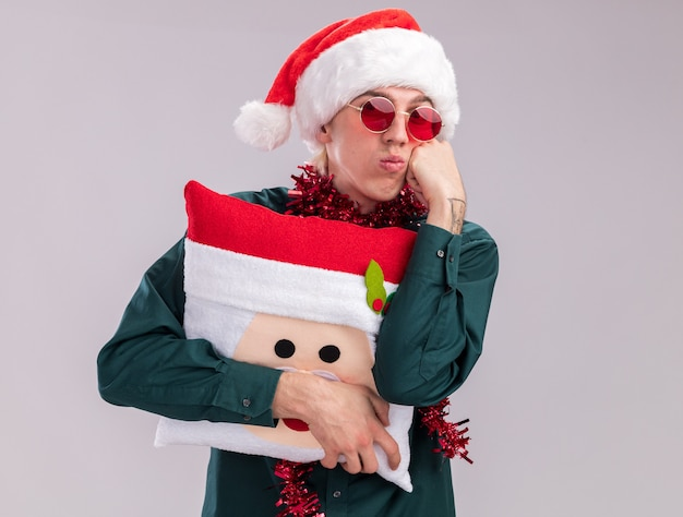Bored young blonde man wearing santa hat and glasses with tinsel garland around neck holding santa claus pillow keeping hand on face looking at camera puffing cheeks isolated on white background