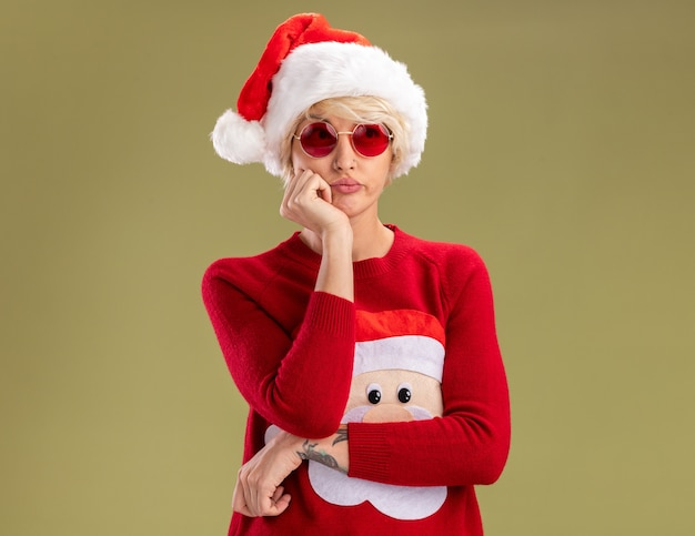 Bored young blonde woman wearing christmas hat and santa claus christmas sweater with glasses keeping hand on chin looking at side isolated on olive green wall with copy space