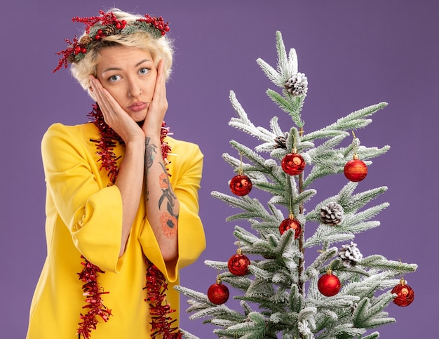 Bored young blonde woman wearing christmas head wreath and tinsel garland around neck standing near decorated christmas tree looking  keeping hands on face isolated on purple wall