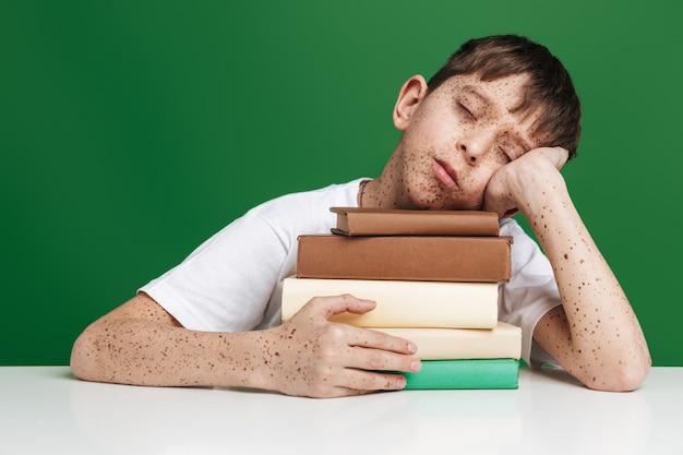 緑の壁の上のテーブルのそばに座っている間、本の上で眠っているそばかすのある退屈な少年