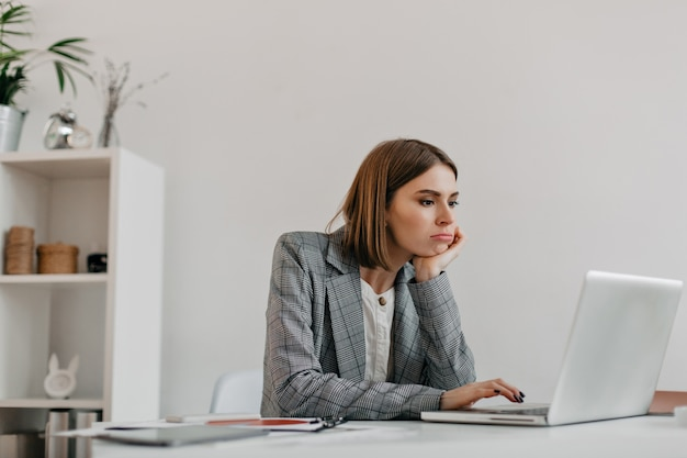 회색 옷에 지루한 젊은 비즈니스 아가씨는 그녀의 직장에서 노트북 화면을 살펴 봅니다.