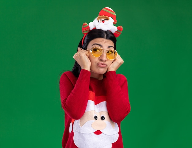 Bored young caucasian girl wearing santa claus headband and sweater with glasses keeping hands on face looking at side with pursed lips isolated on green background with copy space