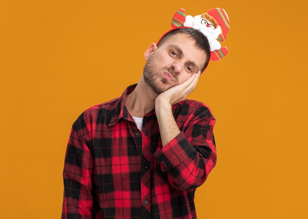 Bored young caucasian man wearing santa claus headband looking at camera keeping hand on face with pursed lips isolated on orange background with copy space
