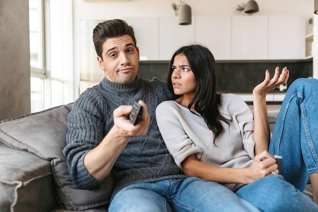 Скучно молодая пара, сидя на диване у себя дома, смотрит телевизор
