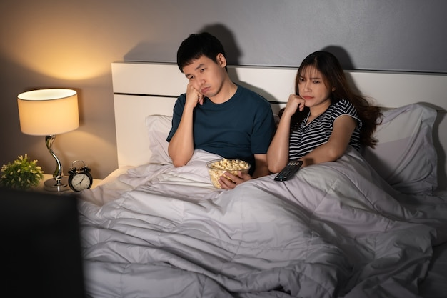 Bored young couple watching tv on a bed at night