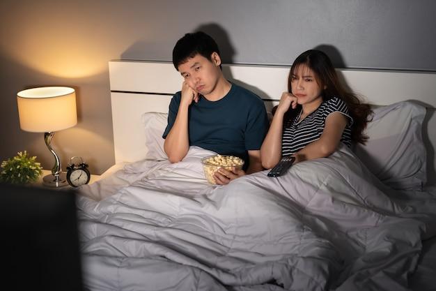夜のベッドでテレビを見ている退屈な若いカップル
