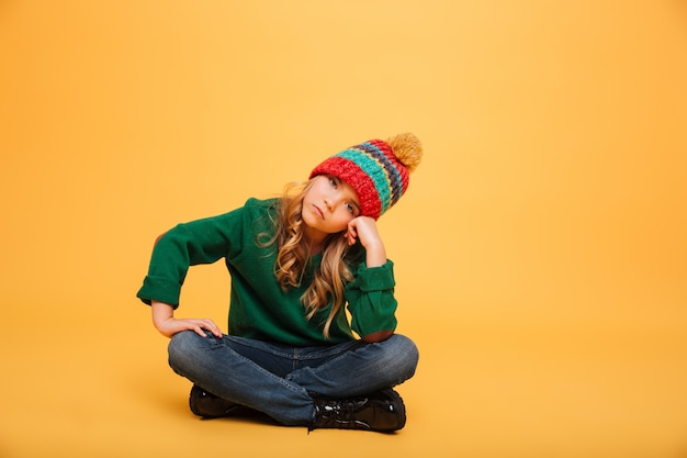 Bored young girl in sweater and hat sitting on the floor while looking at the camera over orange