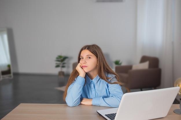 Скучно молодая девушка отдыхает от онлайн-классов