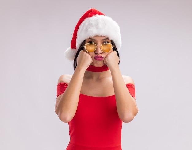 Скучающая молодая девушка в шляпе санта-клауса и очках смотрит в камеру, держа руки на лице с поджатыми губами, изолированными на белом фоне с копией пространства