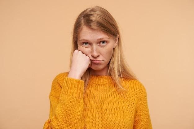 Annoiato giovane femmina adorabile con i capelli sciolti voluminosi che poggia la guancia sulla mano alzata e guarda tristemente, indossa un pullon di senape lavorato a maglia mentre posa sul beige