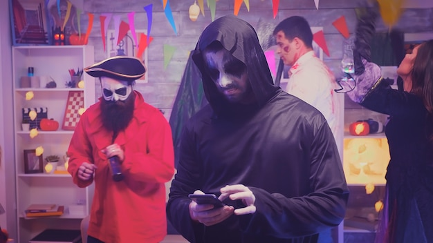 Bored young man dressed up like grim reaper at halloween party.