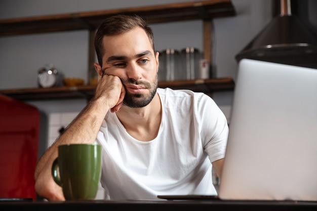 台所のテーブルに座っている間ラップトップコンピューターを使用して退屈な若い男