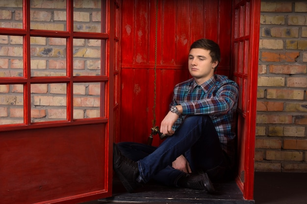 Bored young man waiting for a phone call on a public pay phone sitting on the floor of the booth with a listless expression