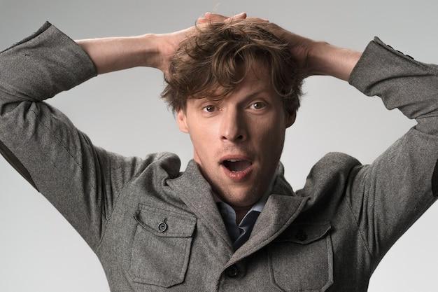 Скучно молодой человек зевает, держась за руки за голову. крупным планом портрет мужчины в повседневной одежде изолированы
