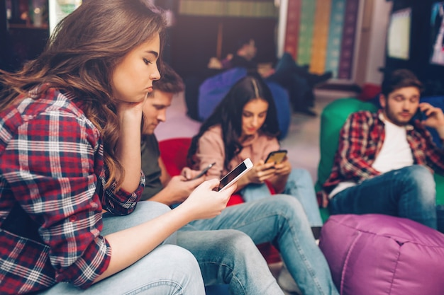 Скучающие молодые люди сидят в игровой комнате и смотрят на фейнов в руках. один парень разговаривает по мобильному телефону. они заняты.