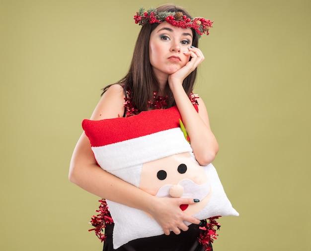 산타 클로스 베개를 들고 목에 크리스마스 머리 화환과 반짝이 갈 랜드를 입고 지루한 젊은 예쁜 백인 여자
