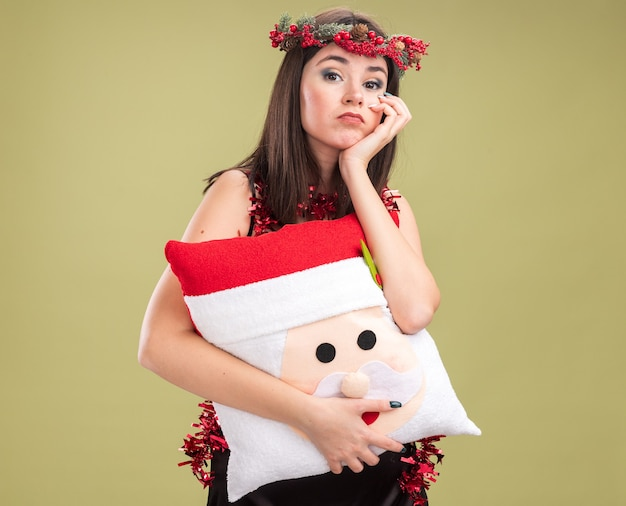 Bored young pretty caucasian girl wearing christmas head wreath and tinsel garland around neck holding santa claus pillow