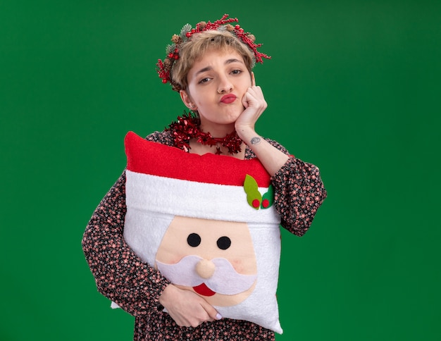 Bored young pretty girl wearing christmas head wreath and tinsel garland around neck holding santa claus pillow keeping hand on chin looking at camera isolated on green background with copy space