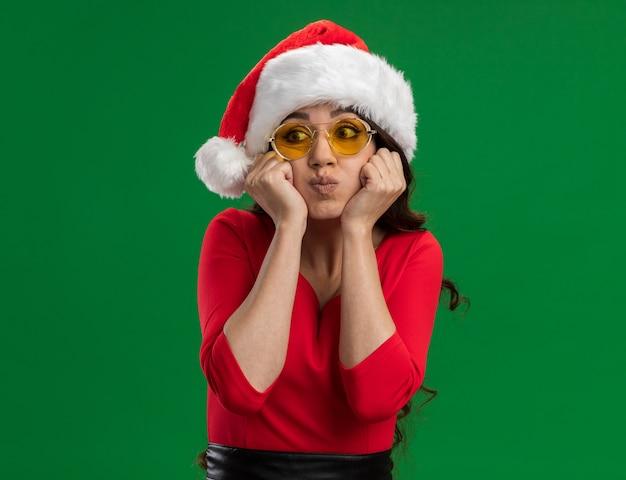산타 모자와 안경을 쓰고 지루한 젊은 예쁜 여자가 복사 공간이 녹색 배경에 고립 된 측면을보고 턱 피 뺨에 손을 유지