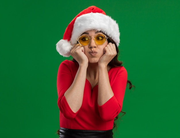 Annoiato giovane bella ragazza che indossa santa cappello e occhiali mantenendo le mani sul mento sbuffando guance guardando lato isolato su sfondo verde con spazio di copia