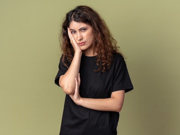 Annoiato giovane bella donna che tiene la mano sul viso guardando la parte anteriore isolata sulla parete verde oliva con spazio copia