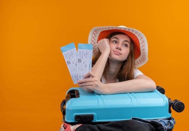 Скучающая молодая девушка-путешественница в шляпе держит билеты на самолет, положив руку на щеку и руку на чемодан на изолированном оранжевом пространстве с копией пространства