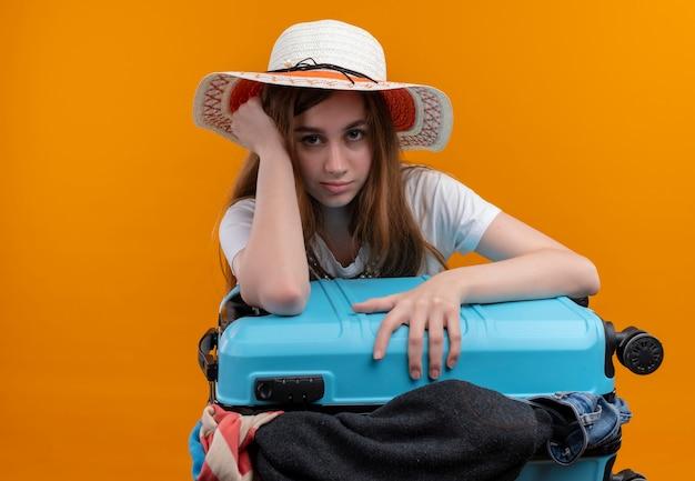 Скучающая молодая девушка-путешественница в шляпе держит чемодан, полный тканей и кладет руку на голову на изолированном оранжевом пространстве с копией пространства