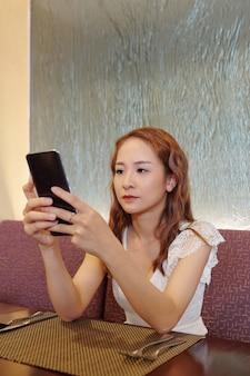 Скучно молодая женщина проверяет свой телефон, ожидая парня за столиком в ресторане