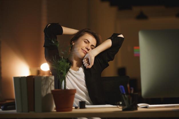 Progettista annoiato della giovane donna che si siede nell'ufficio alla notte