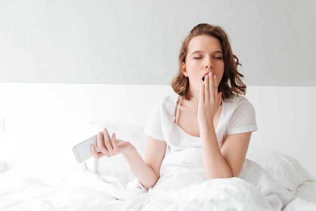 Скучно молодая женщина в постели в помещении с закрытыми глазами зевая
